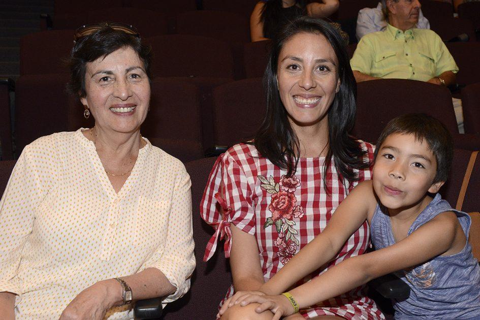 Dos mujeres y un niño sentados mirando a la cámara.