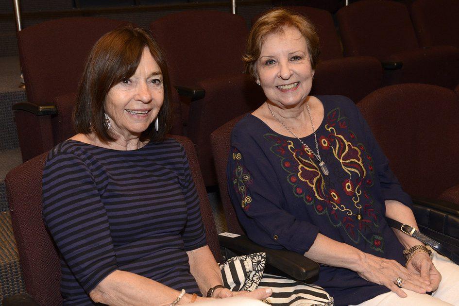 Dos mujeres sentadas mirando a la cámara.