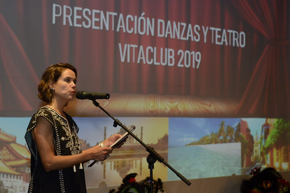 Una mujer arriba de un escenario, hablando frente a un micrófono.